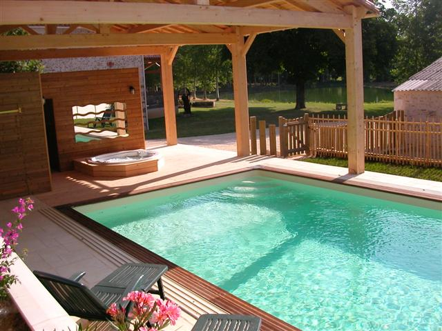 Outdoor swimming pool. sauna and hot tub/Spa with carp lake in background